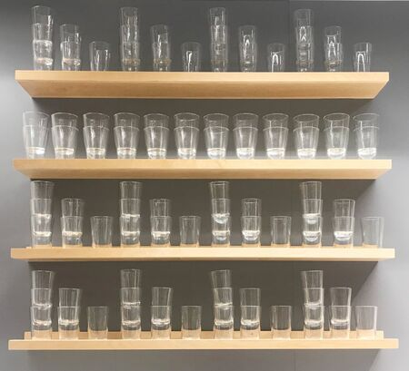 Empty glass decorated on wooden shelf and gray wall