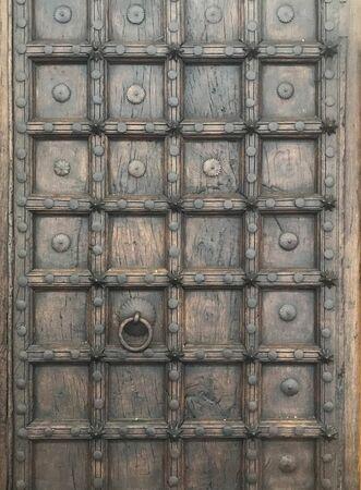 Antique brown wooden door with brass door knocker Reklamní fotografie