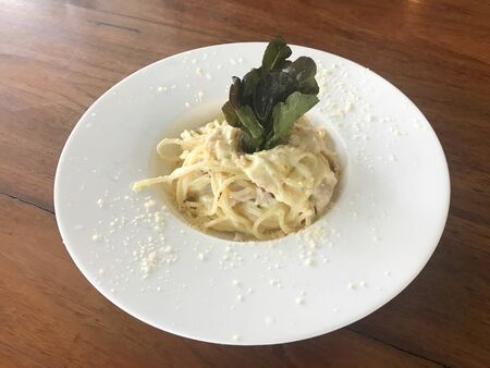 Carbonara spaghetti topped with lettuce and sliced cheese in white dish on wooden table