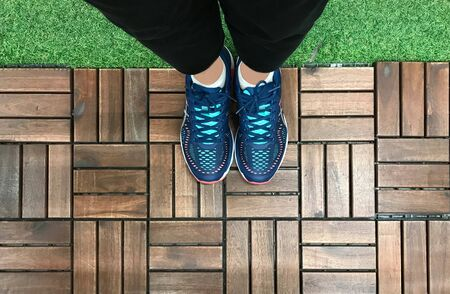 Selfie of feet with blue sneaker shoes on wooden tile and grass floor, top view Stok Fotoğraf