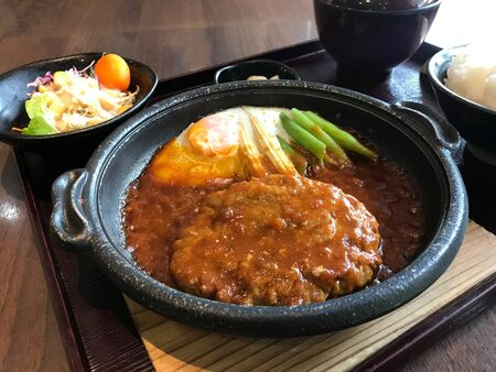 Tasty set of pork hamburger with egg in hot pan served with salad, rice and soup - Japanese cuisine