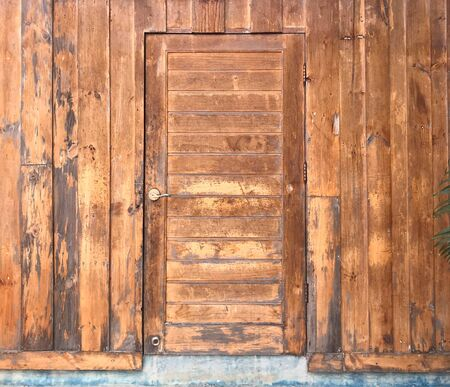 Grunge aged wooden door on wooden wall, architecture concept