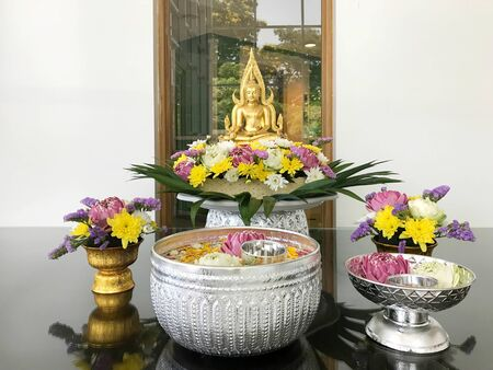 Traditional Thai culture in Songkran festival that will sprinkle water and flower on buddha image