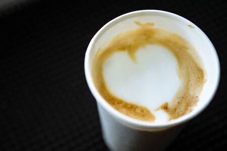 Barista draws milk over a coffee - making latte art for cappuccino