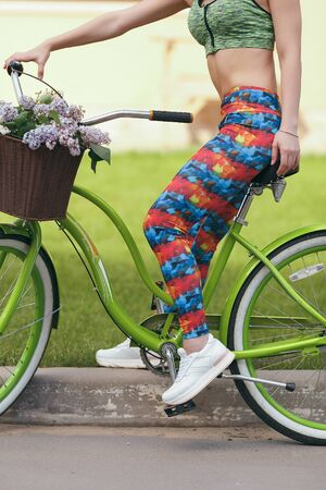 The girl in leggings and top engaged in sports cycling. Spring. The girl is resting and riding a bicycle
