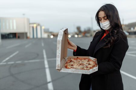 Young woman in medical mask holding cardboard with pizzas going out for food during the epidemic. Concept of takeaway food during quarantine