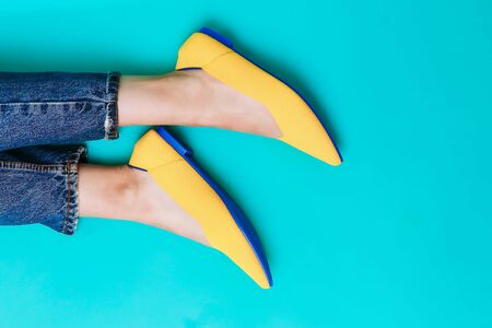beautiful female legs are dressed in stylish yellow shoes without a heel. Light yellow summer sandals on a blue background. Banco de Imagens
