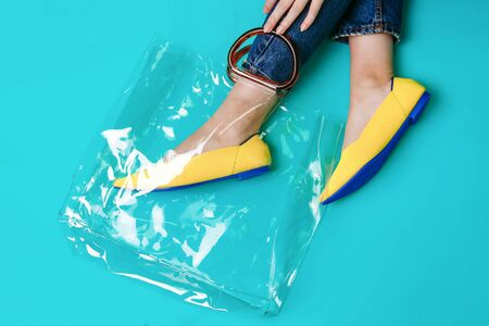 beautiful female legs are dressed in stylish yellow shoes without a heel. Light yellow summer sandals on a blue background and a handbag.