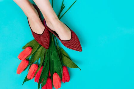 Beautiful female legs are dressed in stylish burgundy flat shoes. Burgundy sandals on a blue background. Imagens