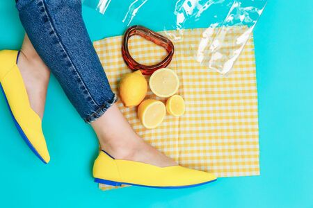 beautiful female legs are dressed in stylish yellow shoes without a heel. Light yellow summer sandals on a blue background against the background of a handbag and bright lemons.