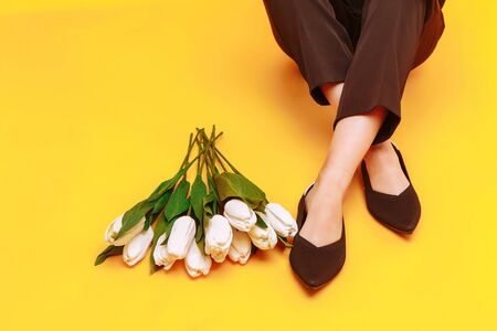 Beautiful female legs are dressed in stylish black flat shoes. black sandals on a yellow background.