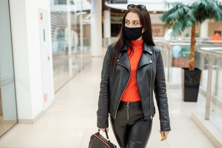 A girl with a medical black mask is walking along a shopping center. Coronavirus pandemic. A girl in a protective mask is shopping at the mall