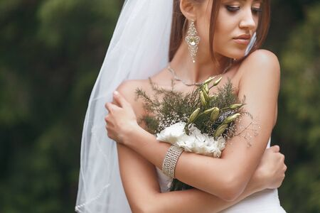 Beautiful bride in a magnificent wedding dress posing among greenery on the street. Bride concept for advertising dresses