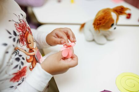 a child in training at home during quarantine makes origami out of paper. childrens creativity. hands close up