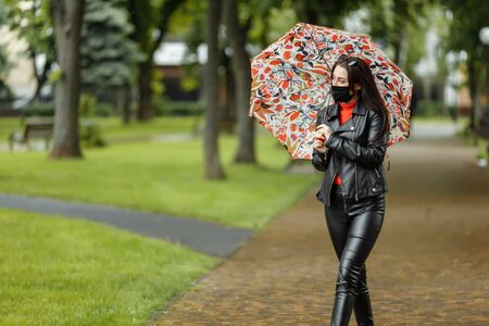 A masked girl is walking along the street. A girl in a protective mask walks in the park with an umbrella in the rain. Coronavirus infection COVID-19