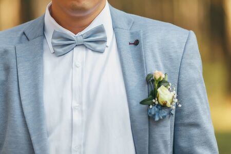 Groom in a blue jacket with a blue bow-tie. On the jacket is a boutonniere of roses.