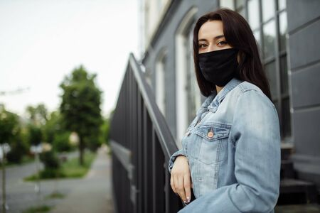girl in a protective mask on a balcony looks at an empty city Stock fotó