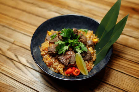 Fried rice with beef and vegetables on wooden background