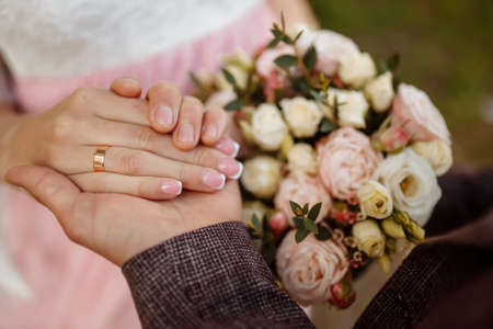 Hands of newlyweds with wedding rings and a wedding bouquetf. newlyweds with wedding rings and a wedding bouquet