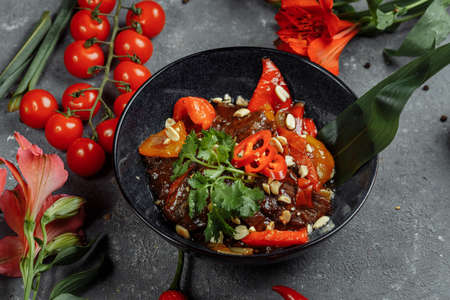 Beef wok. Traditional chinese mongolian beef stir fry in chinese cast iron wok with cooking chopsticks, stone slate background. Top view, copy space
