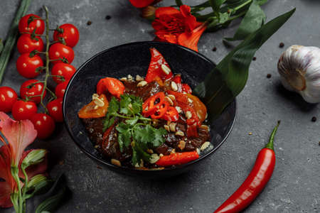 Beef wok. Traditional chinese mongolian beef stir fry in chinese cast iron wok with cooking chopsticks, stone slate background. Top view, copy space.