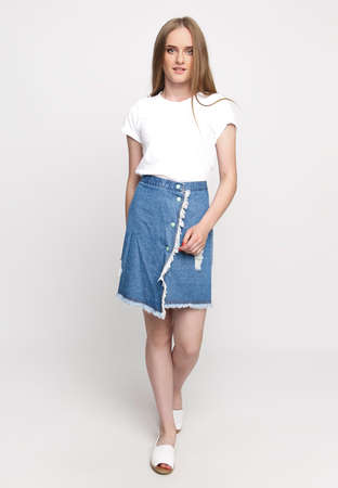 cute young slender woman in a white t-shirt and denim fashionable skirt on a white background. concept of advertising photo for once.