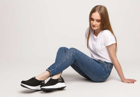 young beautiful woman in a white t-shirt and jeans on a white background. Young woman sit on white background. Photo concept for advertisements of clothes and shoes.