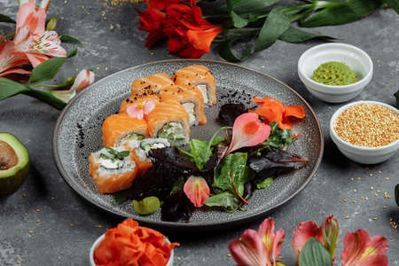 Delicious fresh sushi rolls with salmon and philadelphia cheese on gray plate on dark stone background. Traditional japanese seafood, healthy food concept.