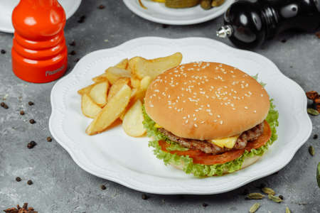 hamburger with fries and salad on the plate.