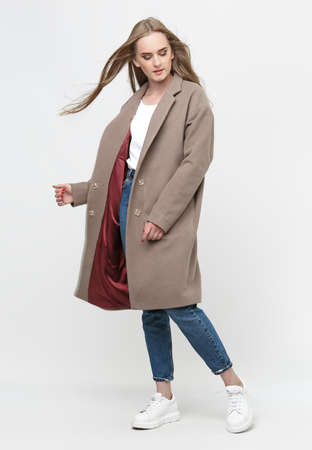 beautiful model posing in a brown long coat on a white background. studio shot. Clothing advertising concept.