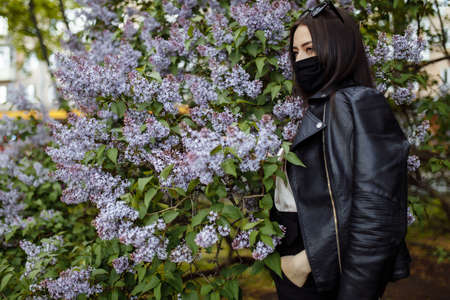 Girl in a medical mask on a background of blooming lilacs. Black mask.