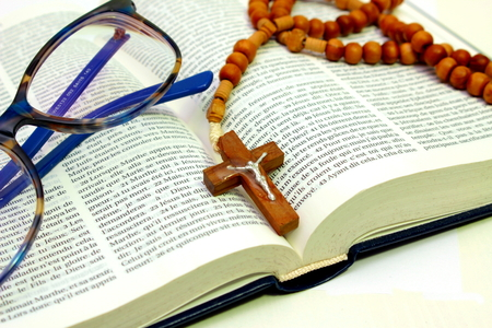 devotional: bible on white with rosary and spectacle