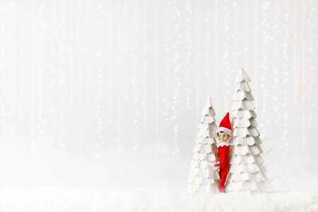 Christmas Elf Hiding Out by Trees on a Snowy Shelf