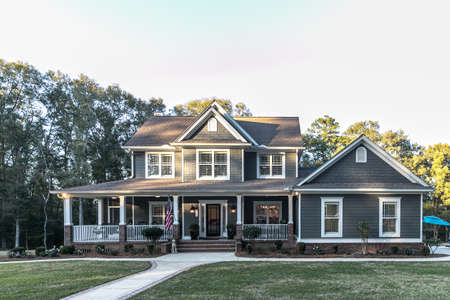 Front view of a large two story blue gray house with wood and vinyl siding