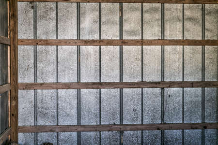 A Grid metal and wood exterior wall taken from the interior