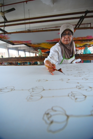 KUALA TERENGGANU ,TERENGGANU - JAN 11 : An artist carefully trace the floral motif on a traditional batik fabric using melted wax on January 11, 2009, Kuala Terengganu, Malaysia