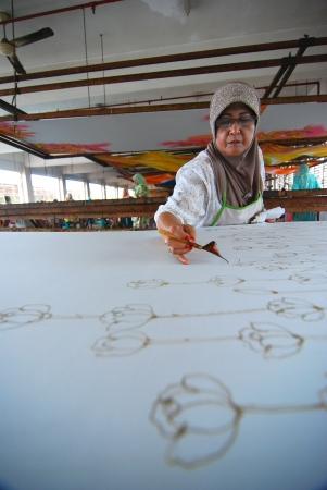 malaysia culture: KUALA TERENGGANU ,TERENGGANU - JAN 11 : An artist carefully trace the floral motif on a traditional batik fabric using melted wax on January 11, 2009, Kuala Terengganu, Malaysia
