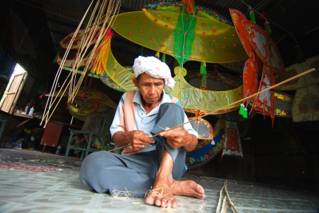 malaysia culture: KOTA BHARU, MALAYSIA - APRIL 7 : The master kite maker, Shafie Bin Jusoh works on his craft in a small hut near the Cahaya Bulan Beach, April 7, 2009 in Kota Bharu, Malaysia