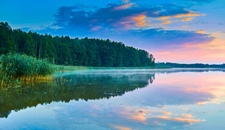masuria: Beautiful panoramic view of the sunset over Lemiet lake in Mazury lake district, Poland. Lake landscape at sunset, fantastic travel destination. Masuria Polish: About this sound Mazury, German: Masuren is a region in northern Poland famous for its 2,000 l Stock Photo