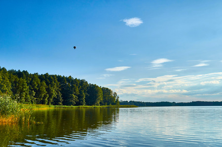 Beautiful panoramic view of the Lemiet lake in Masuria district, Poland with flying balloon. Fantastic travel destination.