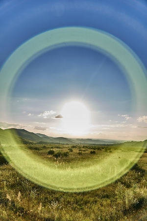 Halo effect around the sun with round rays - beautiful landscape of steppe and stone mountains along the road from the city of Ust-Kamenogorsk to the Sibiny lakes (Sibinskiye Ozora), East Kazakhstan 版權商用圖片