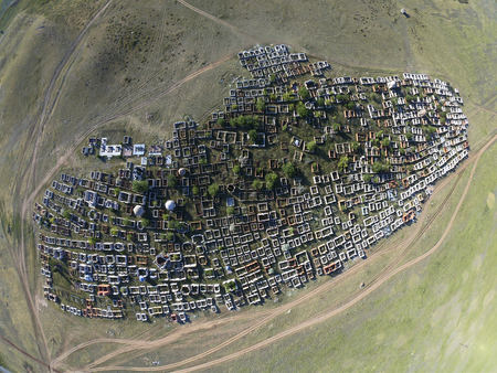 Traditional Kazakh cemetery in the steppe landscape of stone mountains from drone