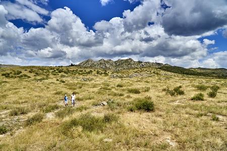 Beautiful landscape of steppe and stone mountains along the road from the city of Ust-Kamenogorsk to the Sibiny lakes (RU: Sibinskiye Ozora: Sadyrkol, Tortkara, Shalkar, Korzhynkol), East Kazakhstan 免版税图像
