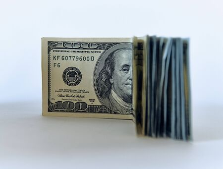 Stack of one hundred dollar bills new design on a white background - The President of USA is watching you with one eye