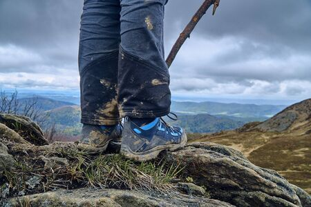 A beautiful panoramic mysterious view of the forest in the Bieszczady mountains (Poland) on a misty rainy spring May day, legs of a young traveler in tourist boots - in the foreground Zdjęcie Seryjne