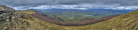A beautiful panoramic mysterious view of the forest in the Bieszczady mountains (Poland) on a misty rainy spring May day, nature is lonely - without people