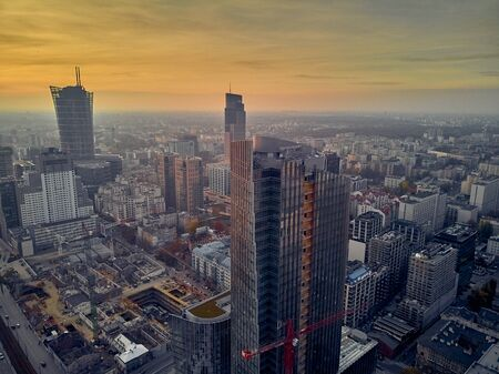 Beautiful panoramic aerial drone view to panorama cityscape of Warsaw modern City, Mennica Legacy Tower (140m) office skyscraper and Warsaw Spire, at sunset in autumn, Warsaw, Poland