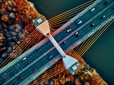 Hermosa vista panorámica de drone aéreo al puente Siekierkowski atirantado sobre el río Vístula y los rascacielos de la ciudad de Varsovia, Polonia en colores otoñales rojos dorados en la noche de noviembre al atardecer - de arriba hacia abajo Foto de archivo