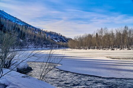 Panoramic view: beautiful spring landscape: the Ulba river in Kazakhstan wakes up from winter sleep - ice drift - snow and ice are melting in the mountains, the bright sun is shining, Qazaqstan