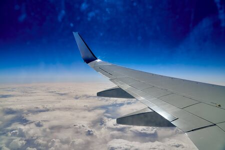 Beautiful panoramic aerial landscape - top view of the wing of an airplane, blue sky, clouds and the earth far below Zdjęcie Seryjne